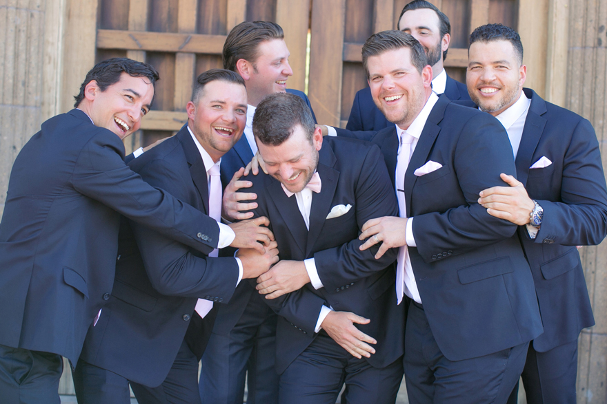 Laughing groomsmen in navy blue with pale pink ties