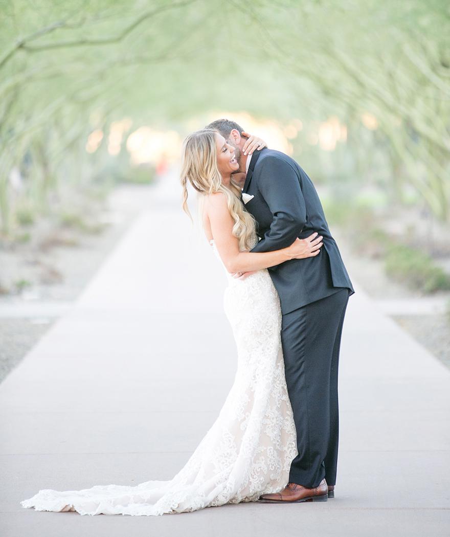 Laughing bride & groom in an avenue of palo verde
