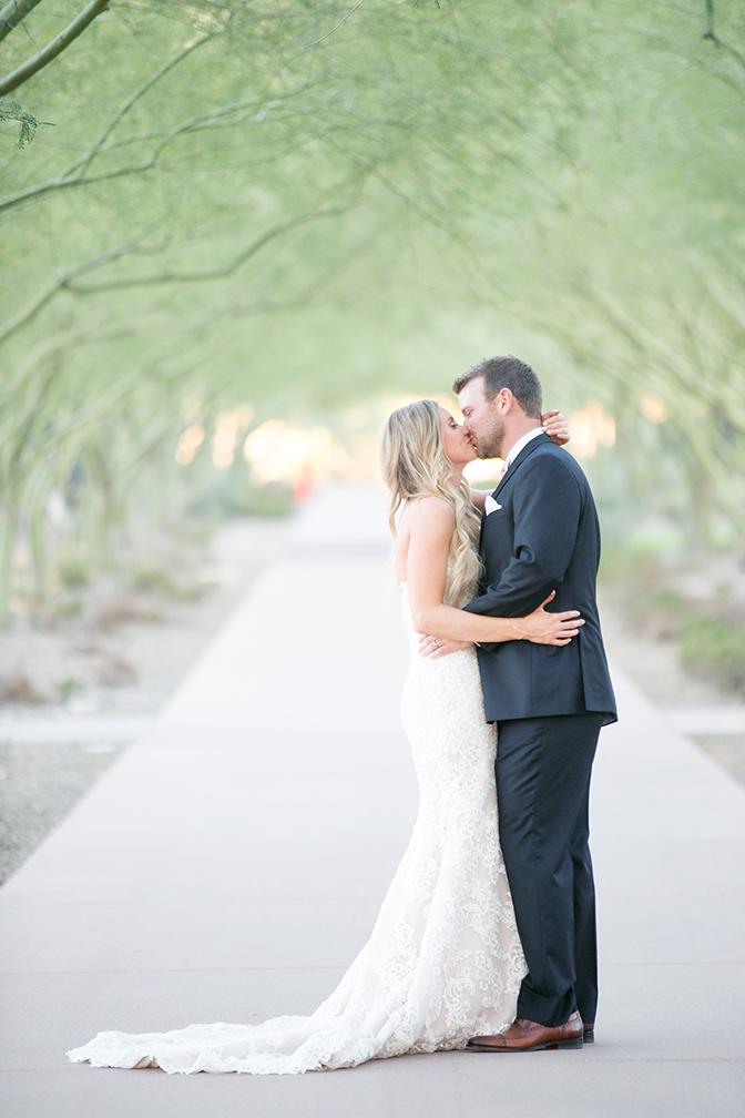 bride & groom kiss in an avenue of palo verde