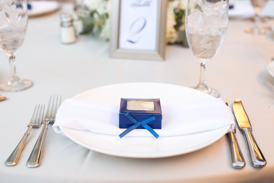 Wedding favors on each plate at an outdoor reception