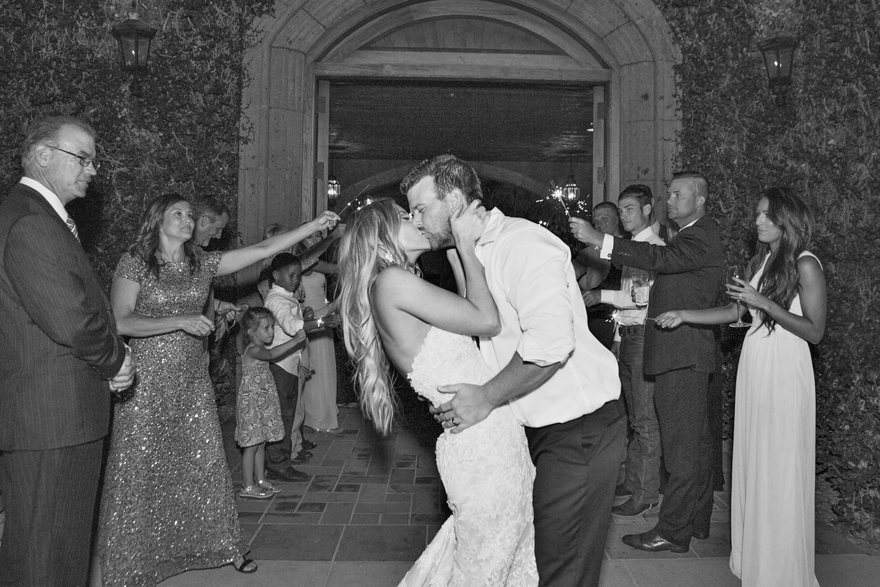 Bride & groom kiss as they exit their wedding reception