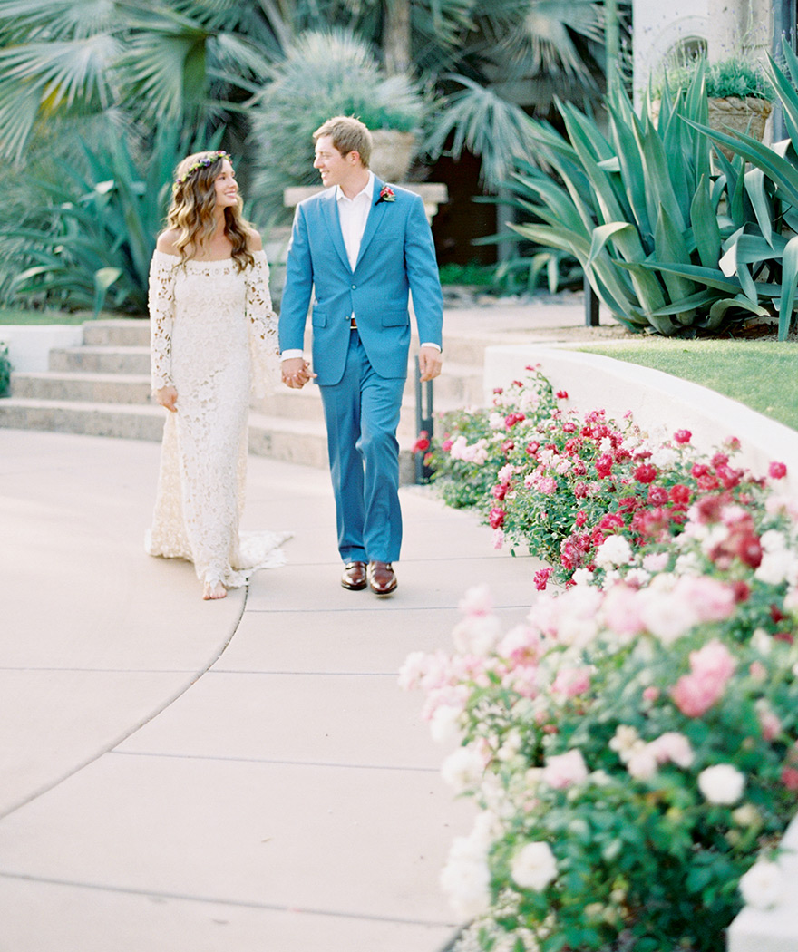 bride in a long-sleeved off-the-shoulder lace bohemian wedding dress and groom in a blue suit