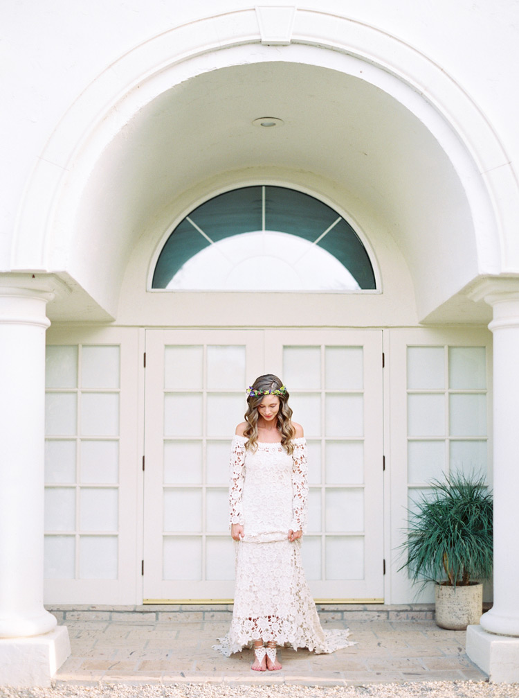 bride in a long-sleeved off-the-shoulder lace bohemian wedding dress and macrame bridal footwear
