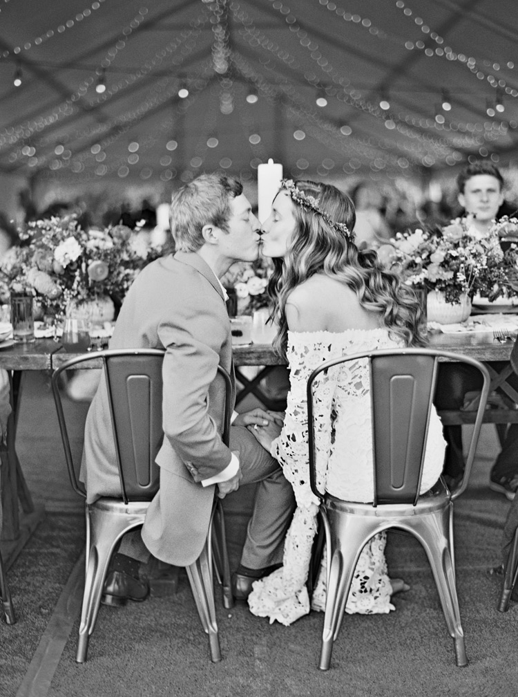 bride and groom kissing at wedding reception dinner