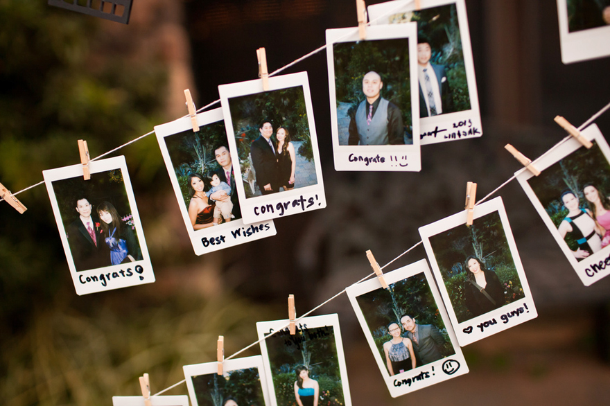 Polaroid prints of family and friends at wedding on hanging wood clips.
