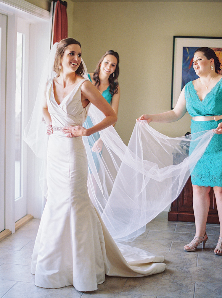 Fit and flare wedding dress and long veil. Wedding photographer capturing bride with her bridesmaids