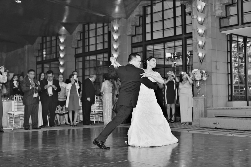 Bride and groom at wedding reception first dance. Black and white photography.