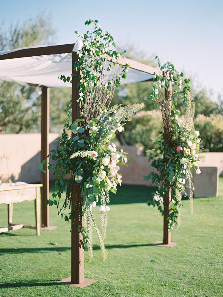 chuppah with pink and cream flowers and lush greenery