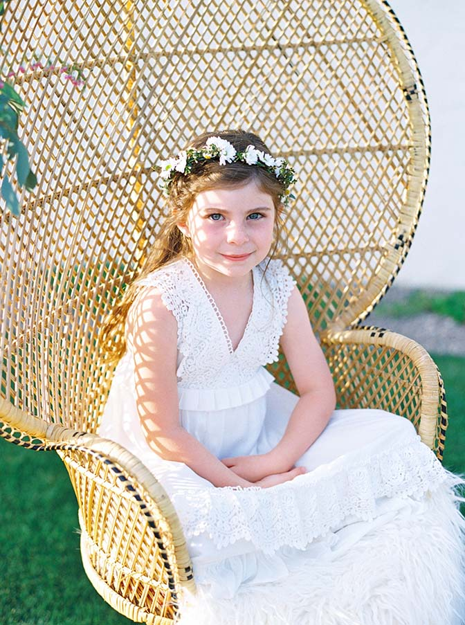 Adorable bohemian flower girl in a rattan peacock chair, DANG! Fine Rentals