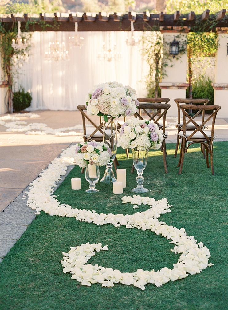 pale flowers, candles, and glass decorate a wedding ceremony