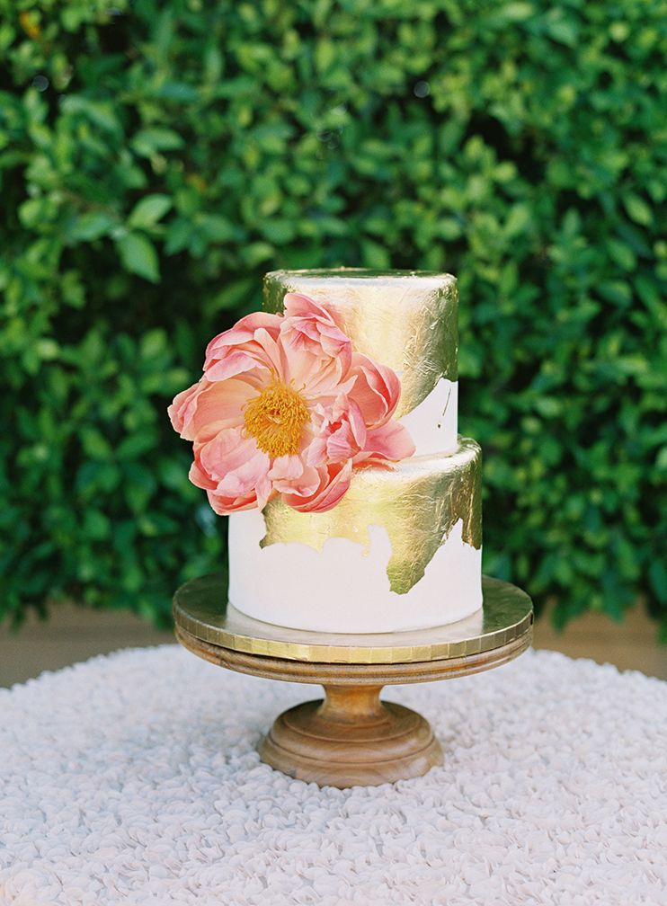 gold leafed wedding cake with a coral peony