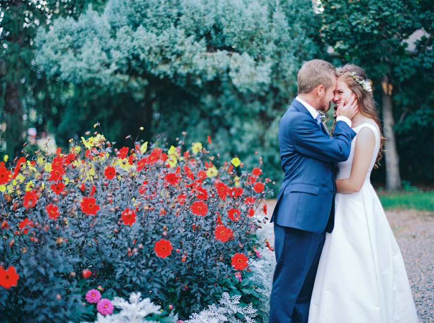 Groom embracing his bride on their wedding day. Beautiful greenery and bright red & yellow flowers.