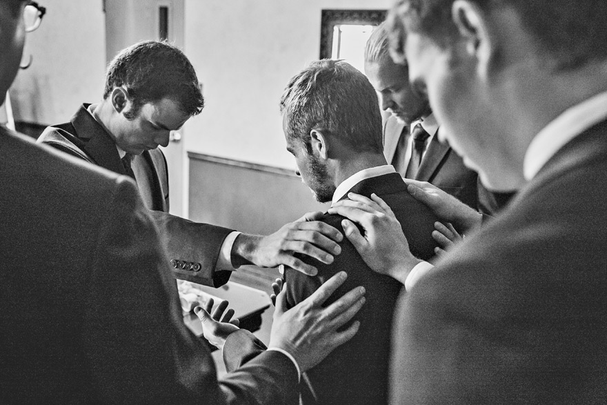 Groom and his groomsmen in prayer before he gets married to his beautiful bride. Black & white photo