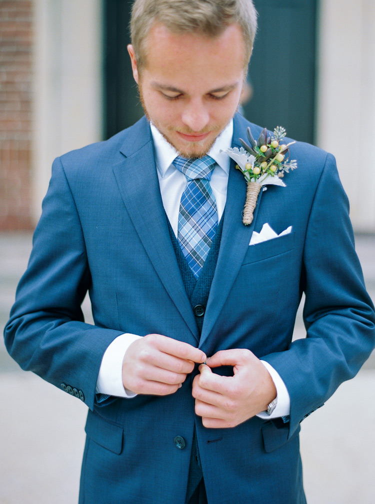 Groom buttoning up his blue suit on his wedding day. Vintage boutonniere ideas.