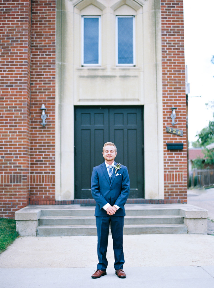 Groom outside church in his blue suit on his wedding day. Vintage boutonniere ideas.