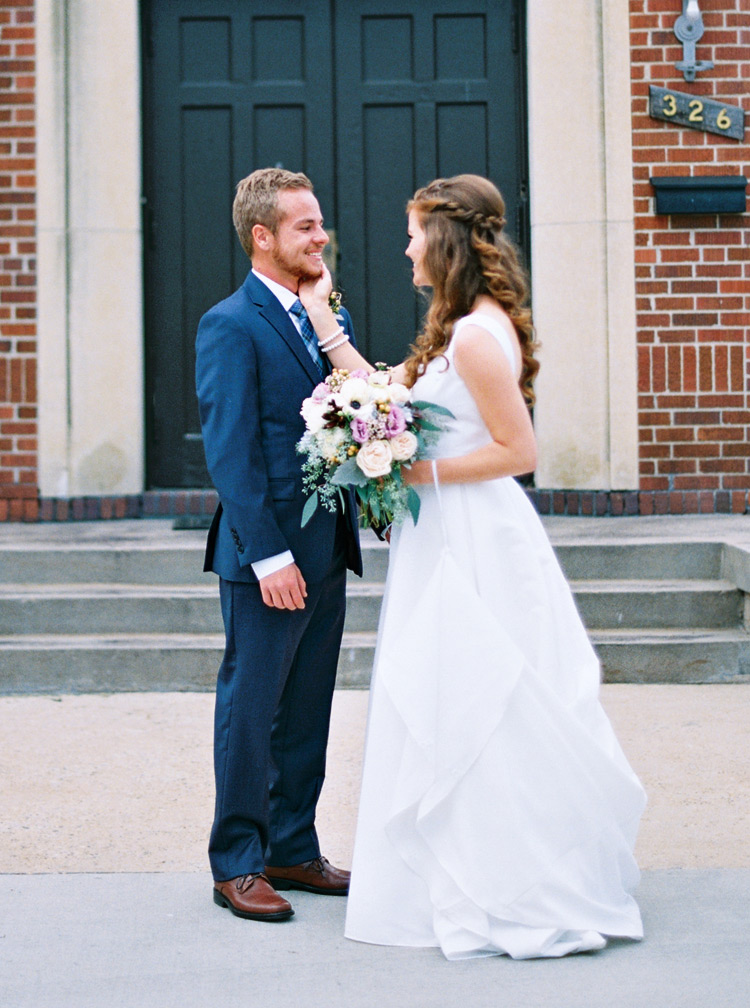 Gorgeous bride smiles at her groom outside of the wedding church in her white simple gown.
