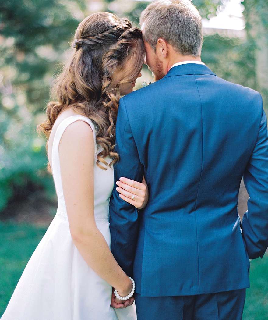 Bride embraces groom in his blue suit. Bridal hairstyle ideas.