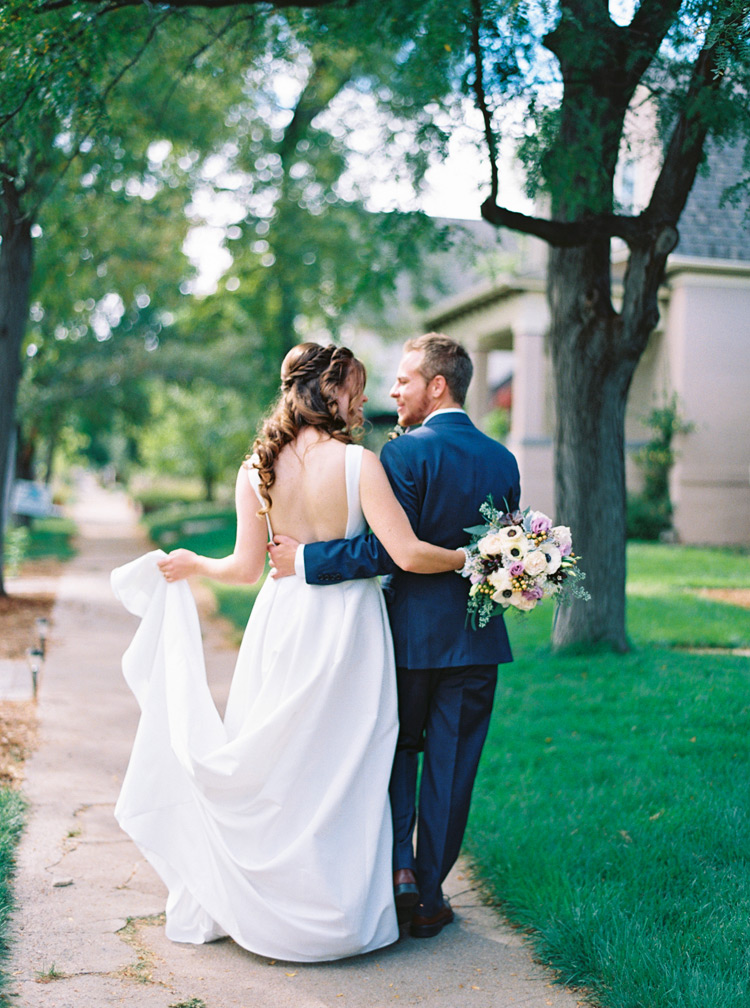 Photograph of bride and groom smiling at each other. Open back dress and bridal hairstyle.
