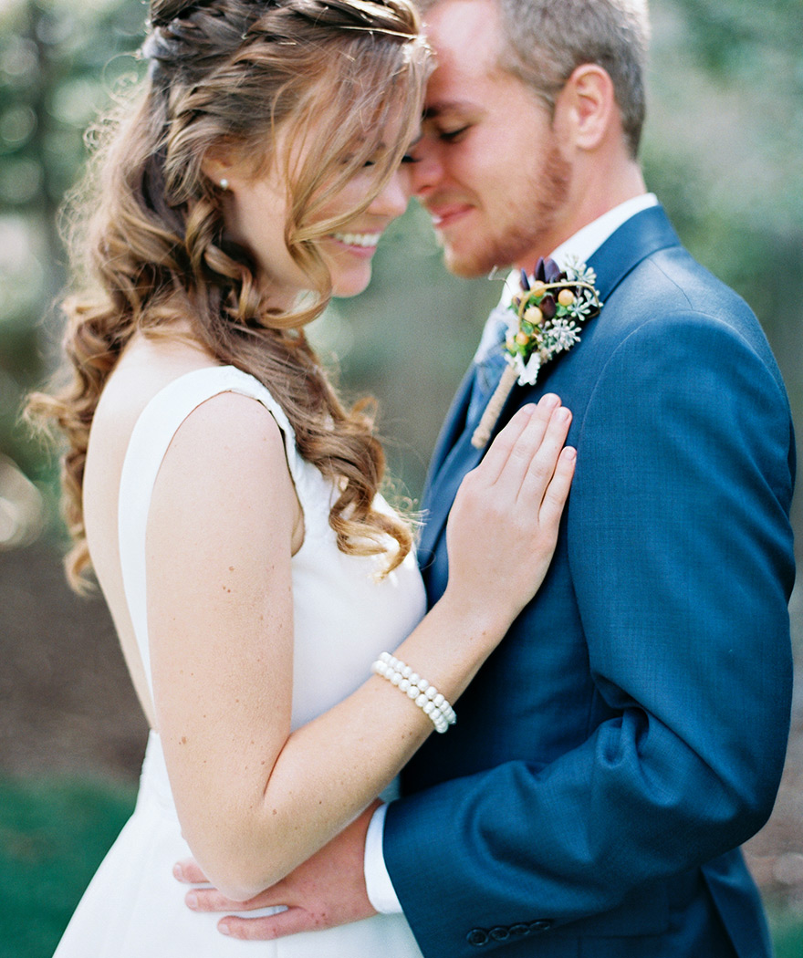 Close up photography of bride and groom. Beautiful wedding hairstyle and pearl bracelets.