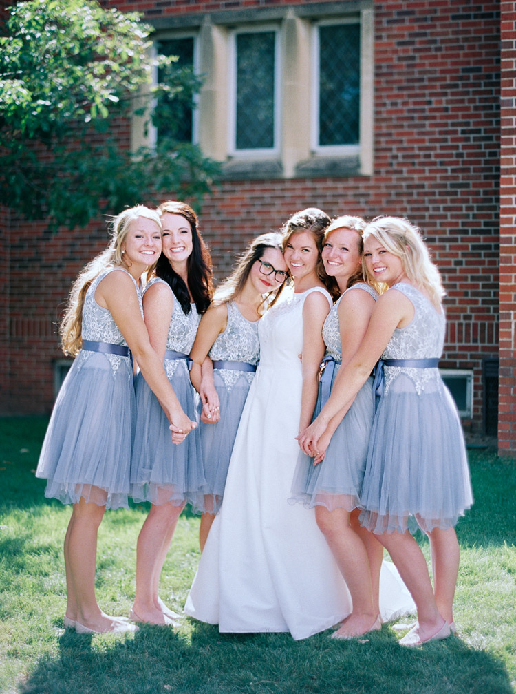 Bride and her bridesmaids on her wedding day. Short periwinkle dresses and flats.