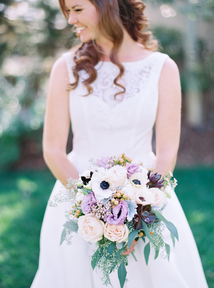 Gorgeous and dramatic bridal bouquet. Floral arrangement with white, purple, and light pink flowers.