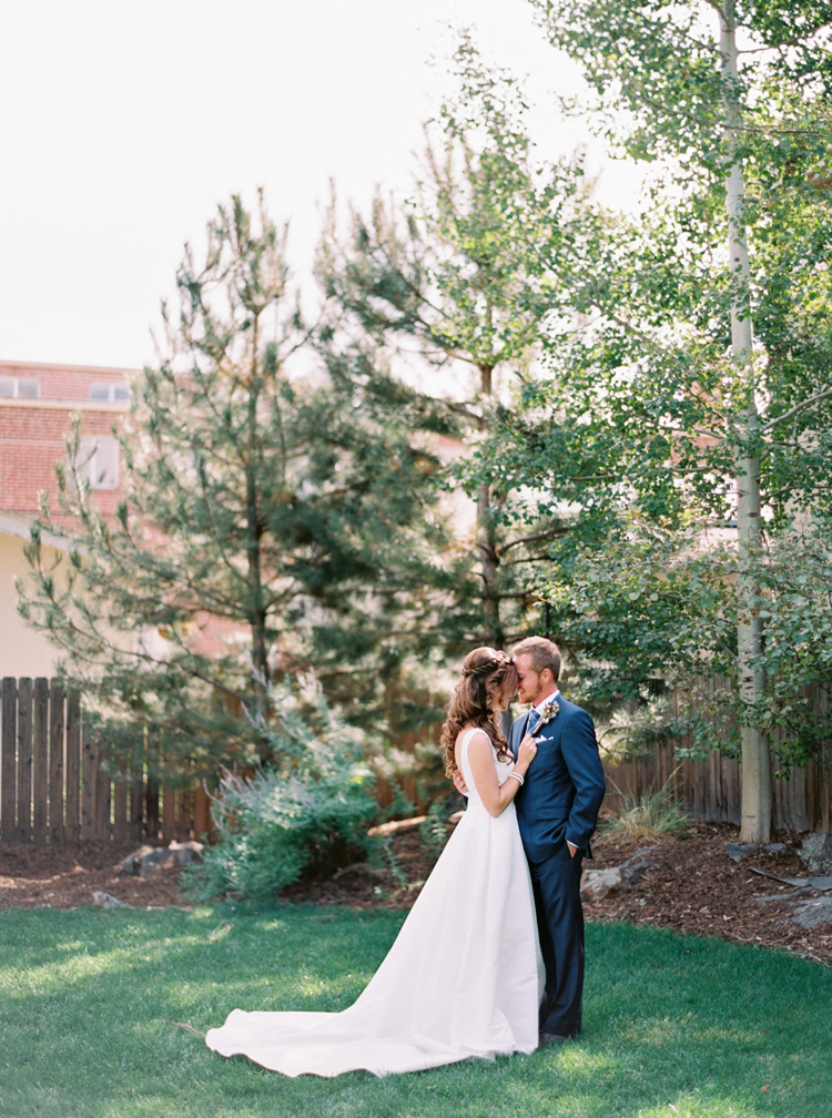 Sweet moment of bride in elegant white dress smiling at groom. Green scenery in Denver, Colorado.