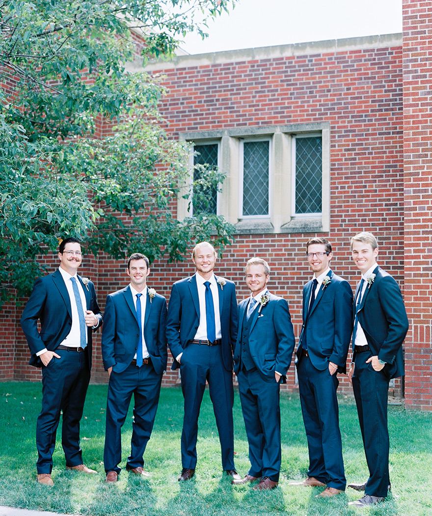 Groom and his groomsmen in blue suits and loafers. Wedding day photography outside church.