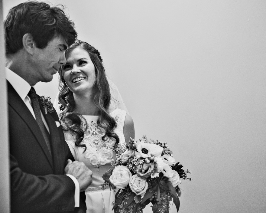 Adorable photograph of bride smiling at her father as he walks her down the isle at her wedding.
