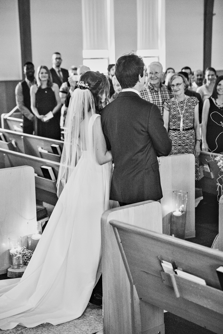 Bride walks down the isle at her vintage inspired wedding in gorgeous veil. Black & white photograph