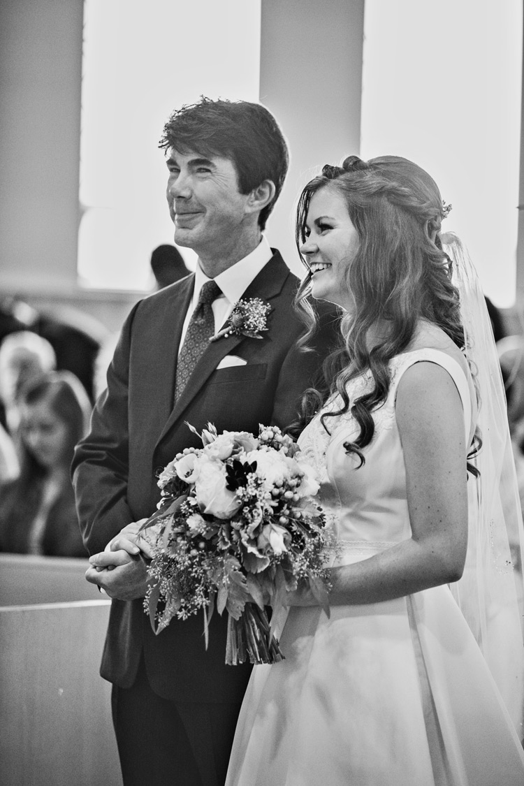 Father of the bride and his daughter walking down the isle on her wedding day. Black & white photo
