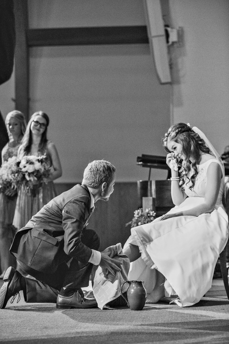 Bride cries as groom performs spiritual foot washing at indoor church wedding ceremony.
