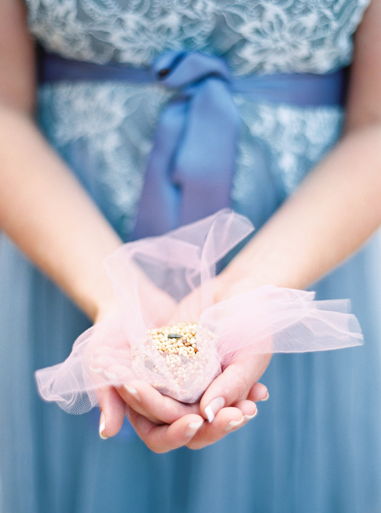 Bridesmaid with french manicure and periwinkle dress holding bird seed to throw at bride and groom