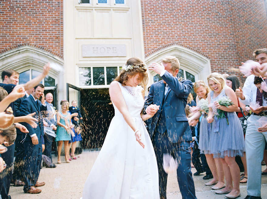 Bride and groom exit the church for their send off getting showered in bird feed instead of rice!