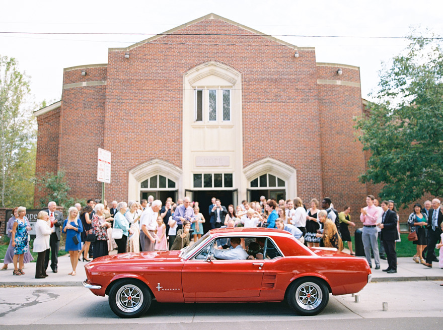 Just Married! Bride and groom send off after the wedding in red vintage Mustang.