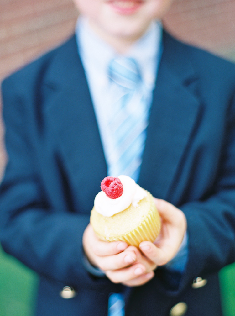 Young boy in adorable blue suit holding a yummy vanilla cupcake at a wedding.