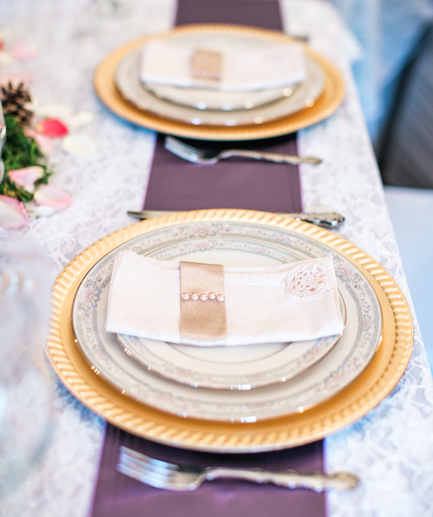 Gorgeous gold and white vintage plate set up for wedding reception. Wedding table settings ideas.