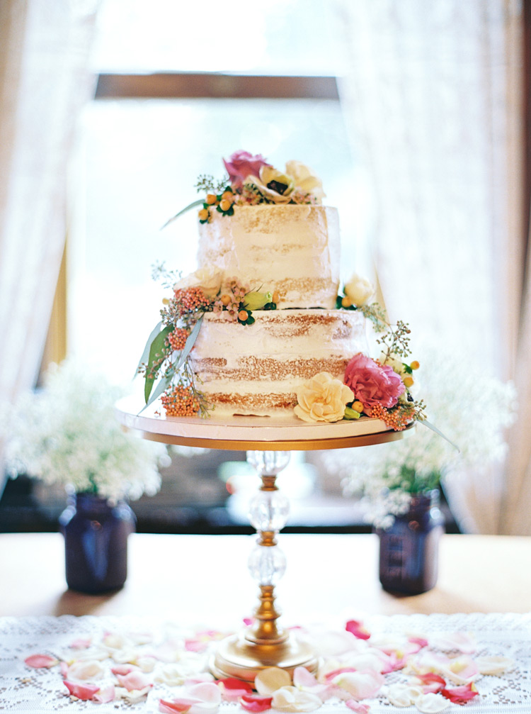 Vintage two-tiered vanilla wedding cake with floral accents and carnations.