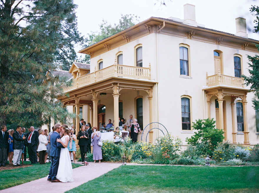 Bride and groom hugging outside of victorian mansion wedding venue in simple and elegant dress.