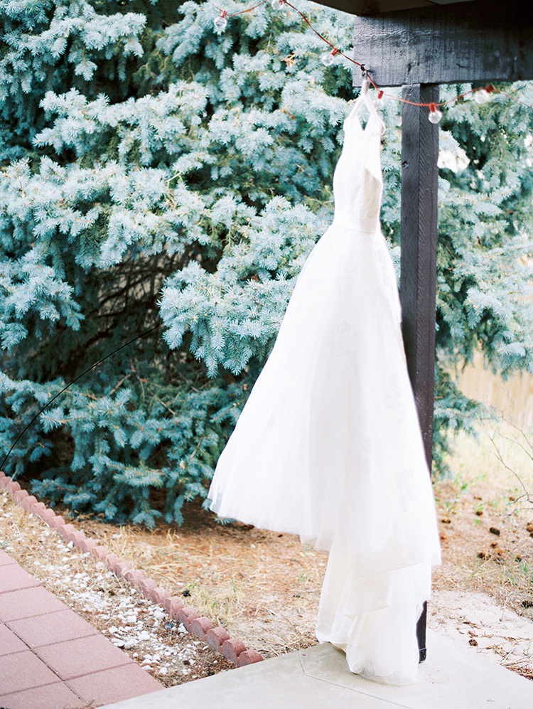 elegant lace wedding dress with beading hanging outdoors