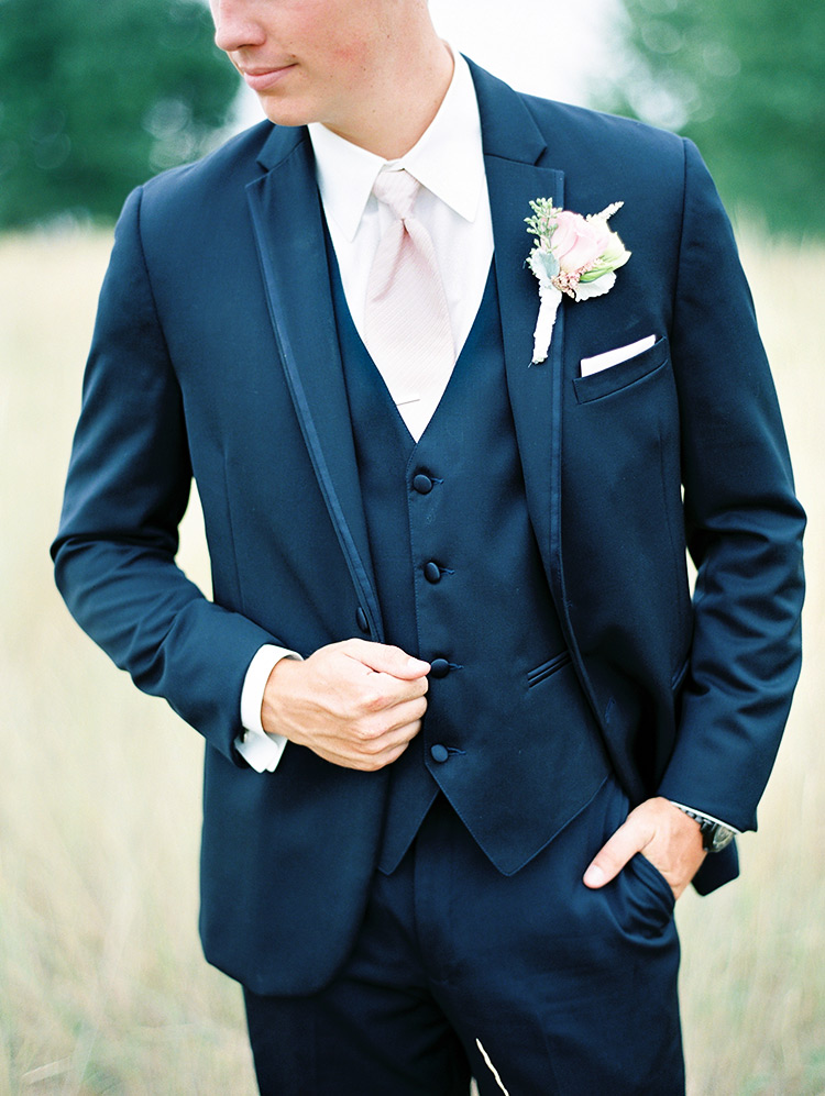 groom wearing a clean cut navy suit with striped white and pink tie