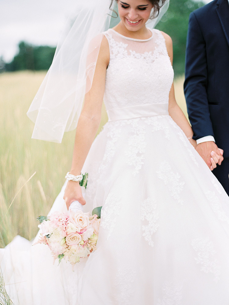 delicate lace wedding dress with beading, veil and bouquet