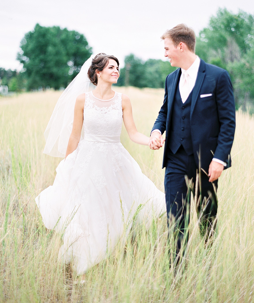 bride wearing delicate lace wedding dress with veil and groom in navy suit