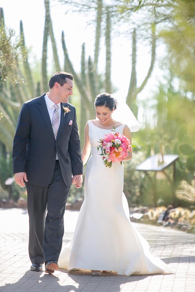 Bride & groom walk hand in hand. Pink wedding bouquet.