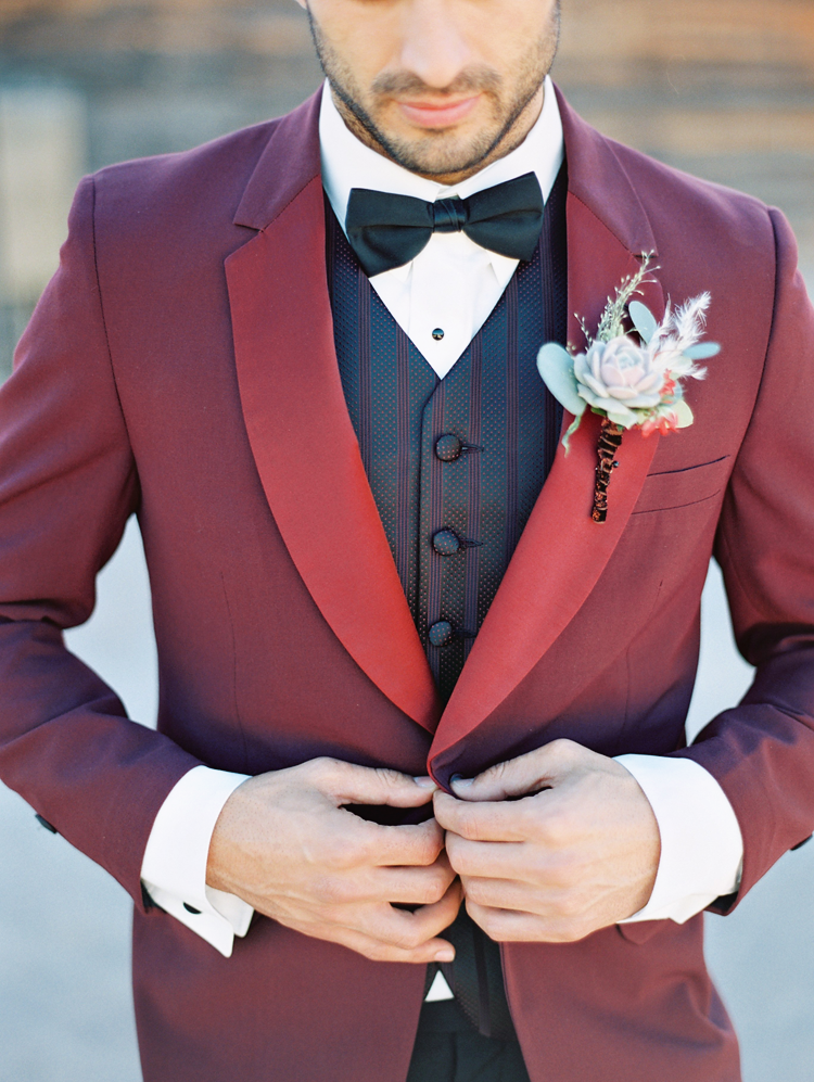 Whimsical but classy - red tux jacket with subtly striped vest for the groom. Amazing boutonniere!