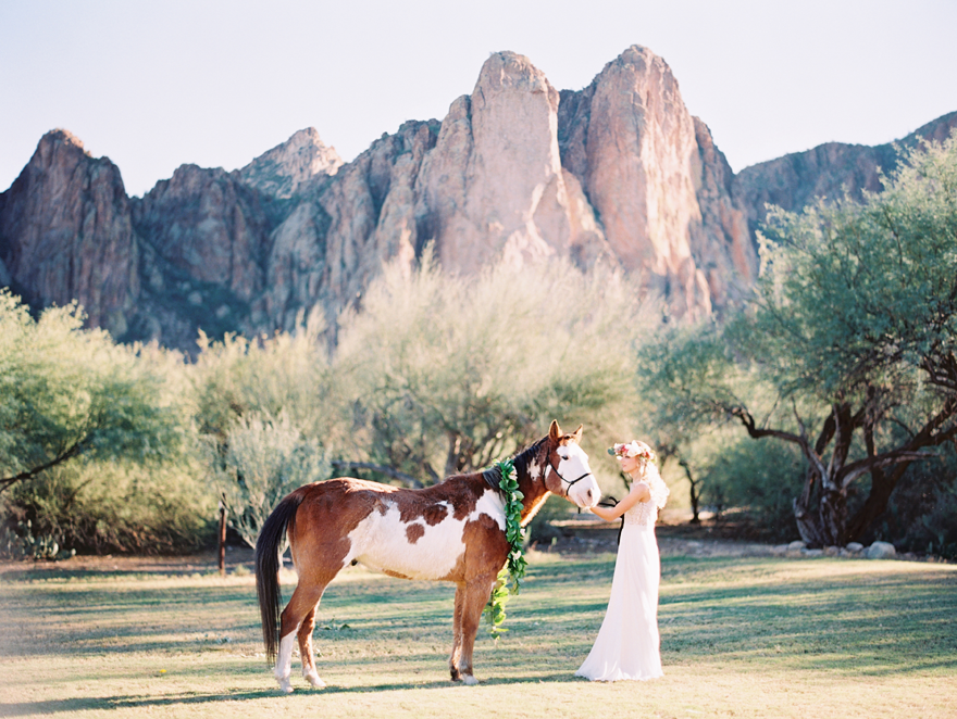 A bride wearing a flower crown pets a pinto horse draped in a garland. Desert wedding inspo