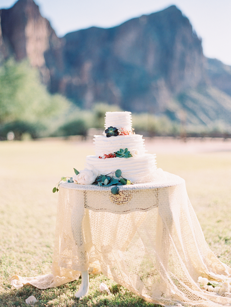 A ruffle wedding cake accented with flowers and succulents stands on a vintage table. Boho wedding