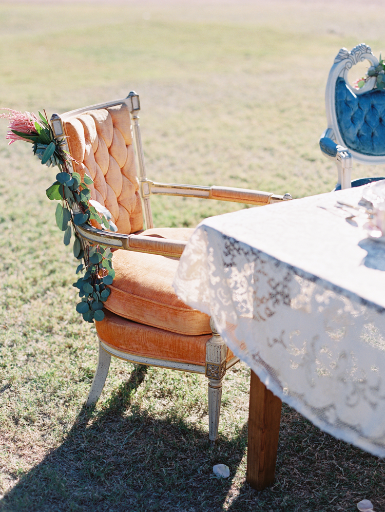 Eclectic vintage furniture with a lace tablecloth for wedding inspiration. Boho wedding style