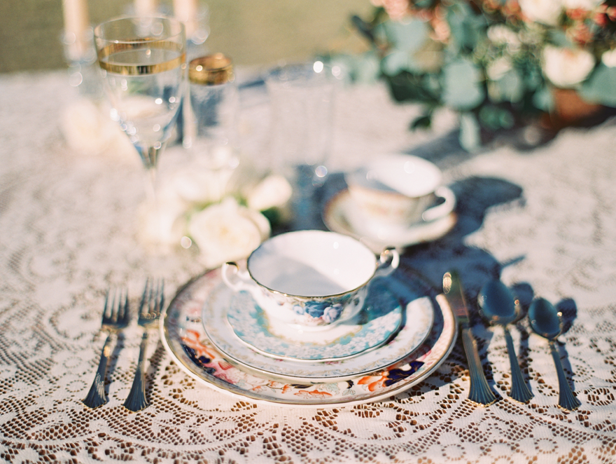 Eclectic vintage china on a lace tablecloth. Boho wedding reception inspiration.