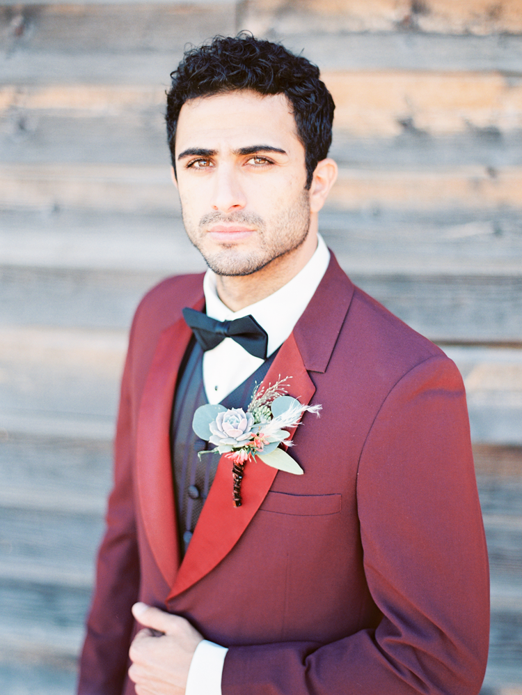 Whimsical but classy groom in a red tux jacket with subtly striped vest. Amazing boutonniere!