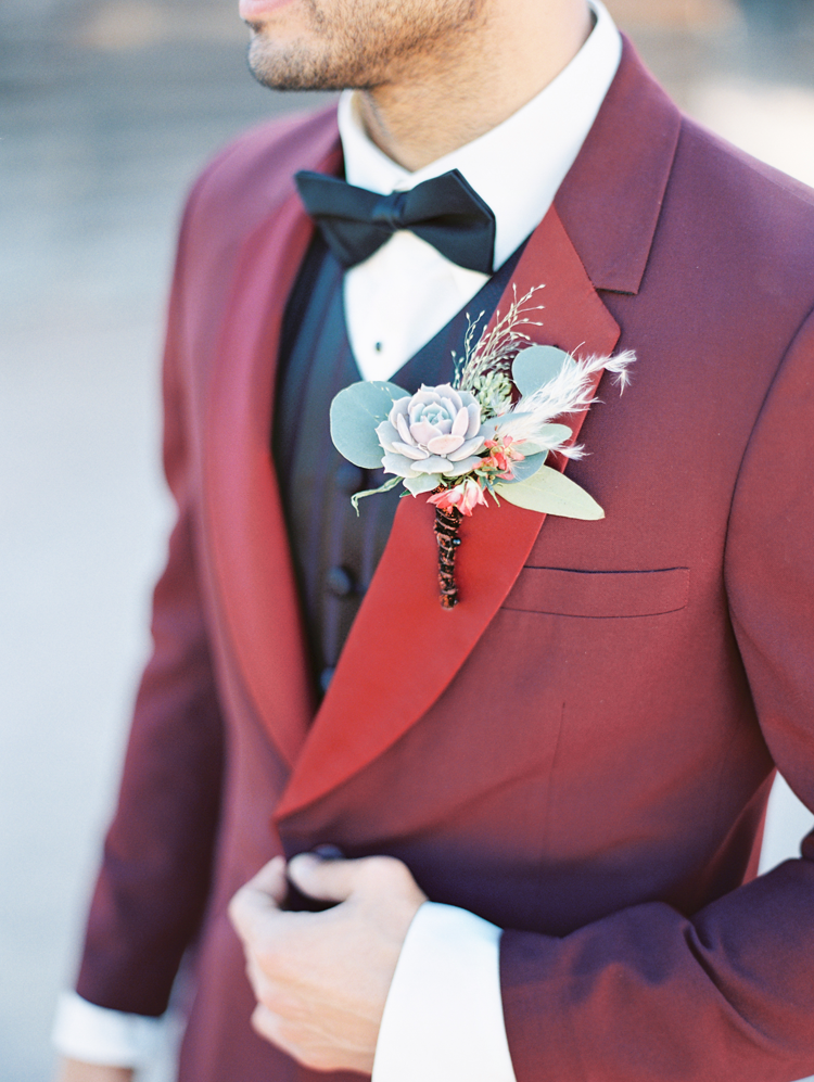 Groom in a red tux jacket with subtly striped vest. Boutonniere of succulent and eucalyptus